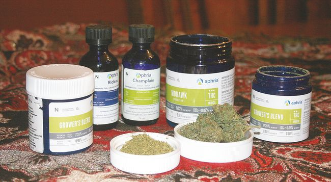 The two skinny tall bottles are oils. Patients take the first one during the day; it doesn't have THC, the active ingredient of marijuana, but maintains relief from pain. The second one is for nighttime and does contain THC. A small amount of these is taken in place of smoking a medicinal cigarette. Other bottles contain medical marijuana in various presentations. In foreground, ingredients are already ground in one and the other is full buds.