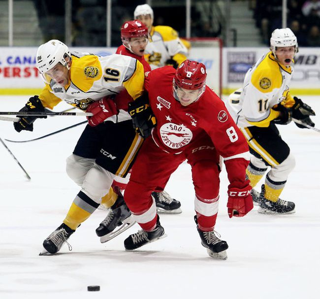 Sarnia Sting's Jordan Ernst (16) and Soo Greyhounds' Jacob LeGuerrier (8) battle for the puck in the first period at Progressive Auto Sales Arena in Sarnia, Ont., on Friday, Oct. 27, 2017. (Mark Malone/Postmedia Network)