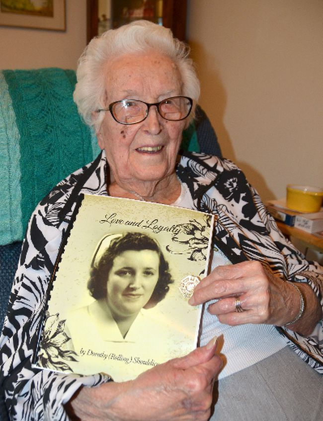 Dorothy Shouldice, who turns 100 on Saturday, with a copy of her memoirs featuring her graduation photo from the General and Marine Hospital School of Nursing in 1939 along with her graduation pin. (Rob Gowan The Sun Times)