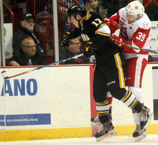 Soo Greyhounds winger Brett Jacklin (left) and Sarnia Sting centre Drake Rymsha collide against the boards during first-period OHL action Wednesday, Dec. 6, 2017 at Essar Centre in Sault Ste. Marie, Ont. JEFFREY OUGLER/SAULT STAR/POSTMEDIA NETWORK