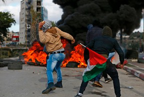 Palestinian demonstrators holding a national flag throw stones towards Israeli troops during clashes that followed protests against a decision by US President Donald Trump to recognise Jerusalem as the capital of Israel, in the West Bank city of Ramallah on December 7, 2017. ABBAS MOMANI/AFP/Getty Images