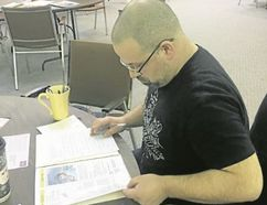 BRUCE BELL/THE INTELLIGENCER Darren Moore of Belleville prepares a letter for a political prisoner during Write for Rights at Bridge Street United Church on Sunday afternoon. The event was hosted by Amnesty International Group III Belleville.