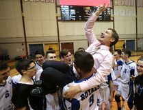 Assistant coach Michael Singleton is hoisted by Nigel Nielsen after the Lord Selkirk Royals defeated the River East Kodiaks in the AAAA provincial high school volleyball championship game at Investors Group Athletic Centre in Winnipeg Dec. 4. (Kevin King/Postmedia Network)