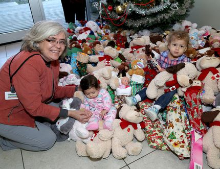 Helen Mabberly, manager of Family and Community Health at Kingston Community Health Centres with Hanna Mohammed, three months and Razan Ellawindy, two years-old, as they sit amongst almost 300 stockings and teddy bears at the Kingston Community Health Centres on Monday December 11 2017. Ian MacAlpine/The Whig-Standard/Postmedia Network
