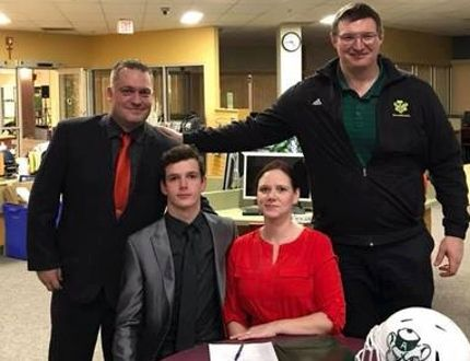 PHOTO SUPPLIED Silas Yelenik signs with the Golden Bears, surrounded by his parents Krys and Lisa Yelenik, and coach Chris Morris