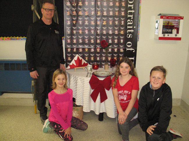 <p>Students with Longue Sault Public School principal Kieran Kennedy at the Fallen Soldier table display are Olivia Stephenson, Katie Crites and Bryson Champagne, on Tuesday, December 12, 2017, in Long Sault, Ont. </p><p>
