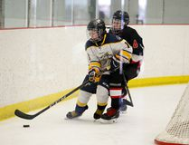 Logan Clow/Daily Herald-Tribune Ethan Banks, right, of the Peace River Colts, tries to muscle Matt Kjemhus, of the Hitch'em Oilfield Hauling Bantam AA Storm, off the puck in ERBHL action at the Crosslink County Sportsplex on Sunday December 10 north of Grande Prairie.