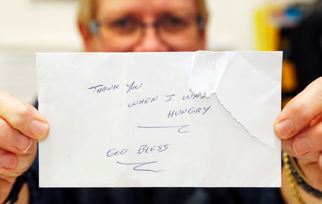Luke Hendry/The Intelligencer Christmas Sharing program co-ordinator Pam Smith holds a donor's grateful envelope at the program office in Belleville. A man who'd registered to receive aid returned the next day to contribute after a sudden change in finances.