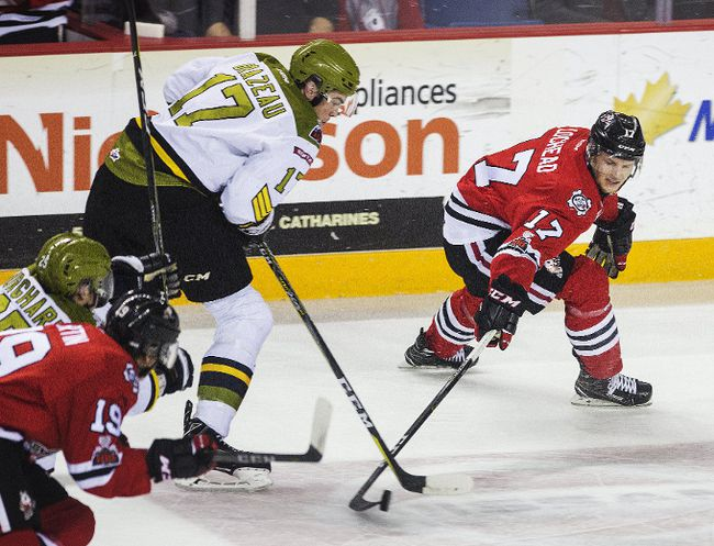 North Bay's Justin Brazeau battles for the puck with William Lochead of the Niagara IceDogs, Friday at the Meridian Centre in St. Catharines. Bob Tymczyszyn Photo