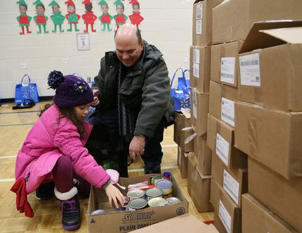 Jillian O'Connor, 7, and her dad, Kevin, prepare Christmas baskets at an event hosted by Club Richelieu Les Patriotes in Sudbury, Ont. on Saturday December 16, 2017. A total of 148 families and individuals in need, received the baskets containing food items. John Lappa/Sudbury Star/Postmedia Network