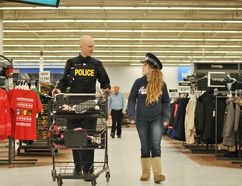 Chatham-Kent Ontario Provincial Police recruit Scott Mosey chats with Megan Krogman during the fourth-annual Shop With a Cop event at the Walmart Chatham Superstore on St. Clair Street Saturday. (Tom Morrison/Postmedia Network)