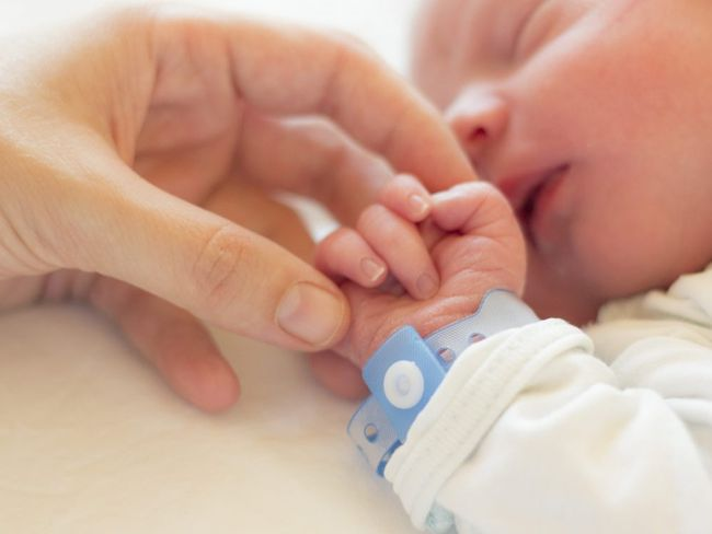 In this stock photo, a newborn baby boy sleeps in his crib while his mother holds his hand. (Getty Images)