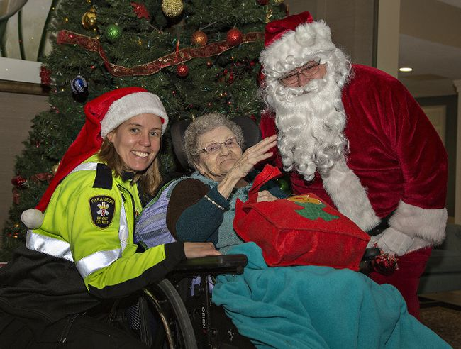 Brant County paramedic Kyia Chopiak and Santa give a gift to Myrtle Tragaskis on Wednesday  at Brierwood Gardens in Brantford. (Brian Thompson/The Expositor)