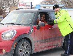 BRUCE BELL/THE INTELLIGENCER Staff Sgt. John Hatch, detachment commander of Prince Edward County OPP, stops Picton and Wellington Tim Hortons owner Paul Massey during the kickoff to the Quinte Region Traffic Coalition Festive R.I.D.E. program Thursday in Rossmore. As expected, Massey only had coffee in the cup.