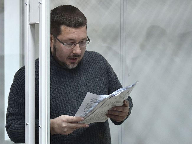 Stanislav Yezhov, a top government interpreter reads documents as he stands in a glass cage at the start of his hearing on suspicion of being a Russian spy at the courthouse in Kiev on Dec. 22, 2017. (GENYA SAVILOV/AFP/Getty Images)