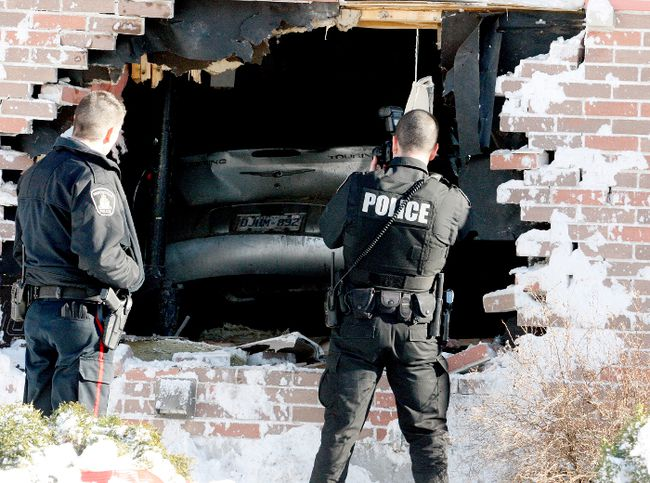 Brockville police officers photograph and investigate the scene of a collision in which a car entered a home on Laurier Boulevard, on Sunday. (RONALD ZAJAC/The Recorder and Times)