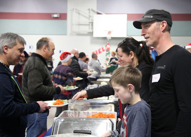 Liam O'Bryne, his dad Sean, mom Ruth and sister Lydia served food during the annual Community Christmas Day Dinner at Father Turcotte school, Monday, Dec. 25, 2017. Olivia Condon/ Fort McMurray Today/ Postmedia Network