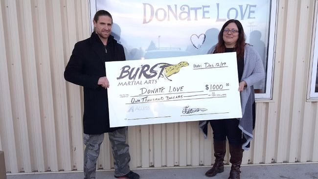 Frank Klassen of Burst Martial Arts presents a donation to Denise Thiessen of Donate Love. (SUPPLIED PHOTOS)