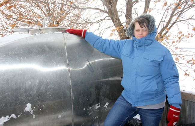 Jessica Brooks, who has had issues with her water well, is shown with her frozen tank on Tuesday.