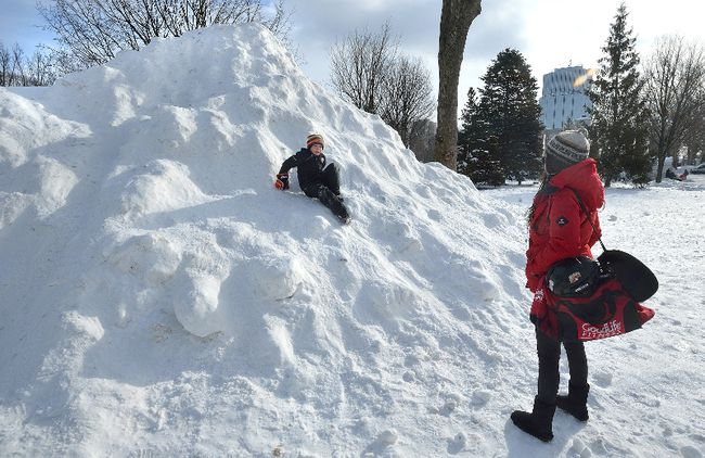 Sharlene Sterkenburg watches as her step-son Tyson Antoine, 8, slides down a giant mound of snow in Victoria Park in London, Ontario on Tuesday, January 2, 2018. (MORRIS LAMONT, The London Free Press)