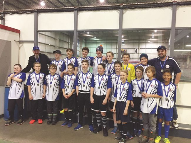 The Beaumont Minor Soccer Association's U14 boys team stands proudly wearing their silver medals at the Edmonton Polar Cup on Dec. 29 with coach Ryan Ruch and assistant coach Iain Ferguson.