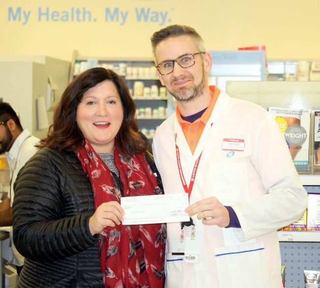 Sharilyn Knox (left), executive director of Central Plains Cancer Services, is presented with a donation from Glen Pauch (right), pharmacist owner at Shoppers Drug Mart Portage la Prairie Thursday afternoon. (Brian Oliver/The Graphic)