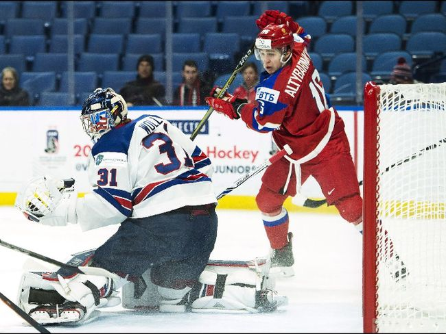 United States goaltender Joseph Woll (31) makes save as Russia forward Andrei Altybarmakyan (16) drives the net during first period quarter final IIHF World Junior Championships hockey action in Buffalo, N.Y., on Tuesday, January 2, 2018. THE CANADIAN PRESS