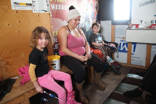 Mira Quesnel and Nolan Merpaw sit next to their mother Kim during their first ice fishing trip on Saturday.