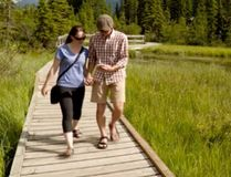 """Above, a couple makes their way across the Policeman's Creek pedestrian bridge in Canmore while solving puzzles as part of the Mystery Town Tours """"outdoor escape room"""" challenge, which takes participants all over town."""