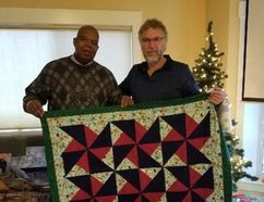 PHOTO COURTESY OF JERRY SHIEL. Jerry Shiel, High River resident, stands with pastor Oliver Johnson, community reintegration chaplain with the Transition Mission Society of Canada, with the presented quilts.