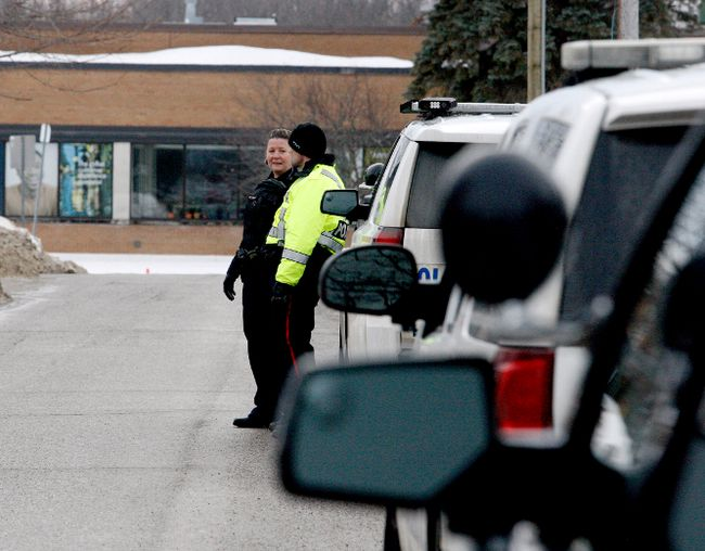 Police officers confer while forming an exterior perimeter around an incident on Havelock Street on Thursday. (RONALD ZAJAC/The Recorder and Times)