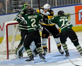 Knights defencemen Evan Bouchard and Alec Regula take a run at Hamilton Bulldog forward Nicholas Caiman after he took a whack at London goalie Joseph Raaymakers during the first period of their OHL game at Budweiser Gardens on Friday night. (MORRIS LAMONT, The London Free Press)