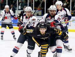 Sarnia Sting's Jordan Ernst (16) squeezes between Windsor Spitfires' Tyler Angle (7) and Thomas Stevenson (22) in the first period at Progressive Auto Sales Arena in Sarnia, Ont., on Friday, Jan. 12, 2018. (Mark Malone/Postmedia Network)