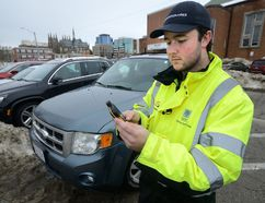 London parking enforcement officer Ian Kerrigan uses a smart phone to write up parking offences on Clarence Street near Victoria Park in London, Ontario on Thursday January 11, 2018 (MORRIS LAMONT, The London Free Press)