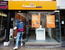 A man enters the store at the new rebranding sign of Freedom Mobile in Toronto on Thursday, November 24, 2016. Nathan Denette / THE CANADIAN PRESS