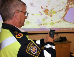 Paramedic services commander Jeff Sager checks out the Waze app while standing next to a Municipal 511 map on Tuesday, Jan. 16, 2018 in Stratford, Ont. (Terry Bridge/Stratford Beacon Herald/Postmedia Network)