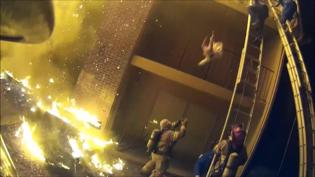 A screenshot of Dekalb County Fire Rescue Department firefighters rescuing trapped occupants from an apartment with heavy fire involvement on arrival. (Local 1492/Facebook)