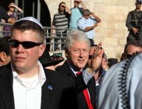 Former US president Bill Clinton (C) waves upon his arrival at the Western Wall in Jerusalem's Old City for a visit to Judaism's holiest site on November 15, 2009. Clinton said ahead of the opening of a museum and centre in Tel Aviv dedicated to Israel's assassinated prime minister Yitzhak Rabin on November 14 that he believes there would have been a comprehensive peace in the Middle East a decade ago if Rabin had not been assassinated. AFP PHOTO/SHAI COHEN