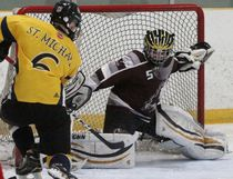 St. Michael's Charlie Rankin can't corral a pass in front of Northwestern's goalie Chayse Zehr during the Huron-Perth high school hockey game Tuesday afternoon at the Rotary Complex in Stratford. St. Mike's won 3-1. (Cory Smith/The Beacon Herald)