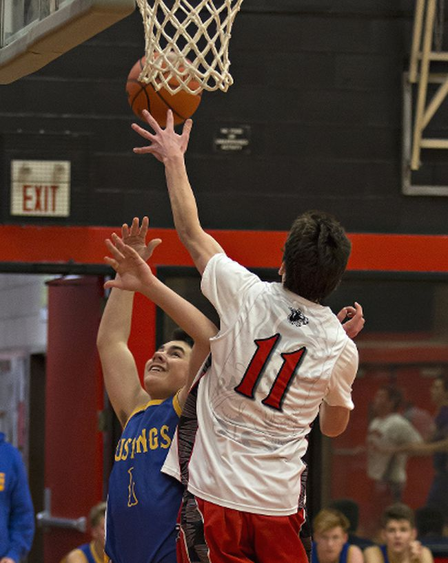 Eli Bastien of Paris District High School goes up to block a shot by Sam Drekic of Brantford Collegiate Institute a high school senior boys basketball game. (Brian Thompson/The Expositor)
