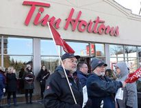 Members of Ontario Federation of Labour protest outside a Tim Hortons Franchise in Toronto on Wednesday January 10, 2018. Protesters angered by some Ontario Tim Hortons franchisees who slashed workers' benefits and breaks after the province raised minimum wage will demonstrate across the country tomorrow. (THE CANADIAN PRESS/Chris Young)