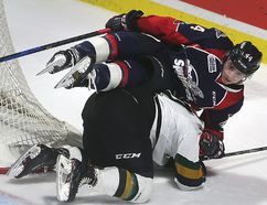 Nathan Staios of Windsor Spitfires tumbles over Nathan Dunkley of the London Knights during their OHL game in Windsor on Thursday night. (DAN JANISSE/Postmedia News)