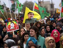 "Syrian-Kurds carry portraits depicting jailed leader of the Kurdistan Worker's Party Abdullah Ocalan, as they protest in Jawadiyah. Syria, after Turkish President Recep Tayyip Erdogan vowed to launch an operation against towns in Syria held by the Kurdish People's Protection Units, which Ankara considers ""terrorists."" (DELIL SOULEIMAN/Getty Images)"
