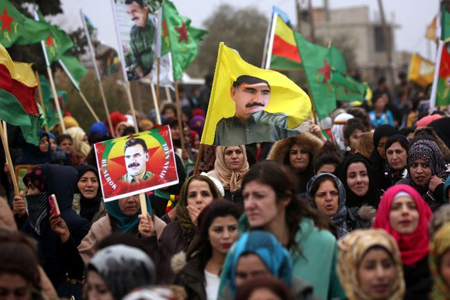 """Syrian-Kurds carry portraits depicting jailed leader of the Kurdistan Worker's Party Abdullah Ocalan, as they protest in Jawadiyah. Syria, after Turkish President Recep Tayyip Erdogan vowed to launch an operation against towns in Syria held by the Kurdish People's Protection Units, which Ankara considers """"terrorists."""" (DELIL SOULEIMAN/Getty Images)"""