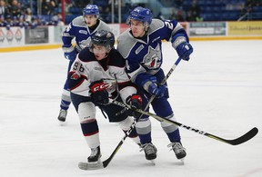Peter Stratis, right, of the Sudbury Wolves, and Damien Giroux, of the Saginaw Spirit, battle for position during OHL action at the Sudbury Community Arena in Sudbury, Ont. on Friday January 19, 2018. John Lappa/Sudbury Star/Postmedia Network