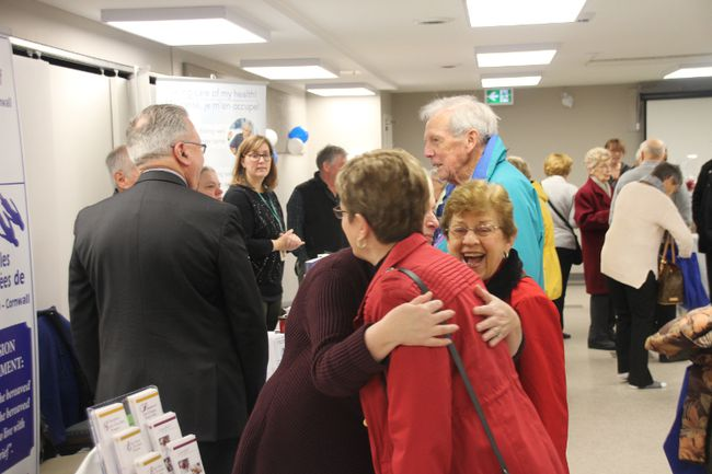 Members of the Seaway Seniors Club embrace at the grand opening of the club's new location at Pitt Street on Saturday.
