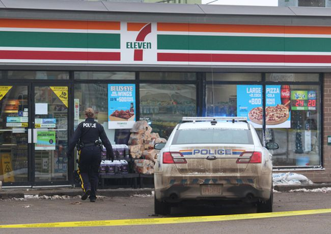 An RCMP officer heads into the 7-Eleven along 99 Avenue on Monday.