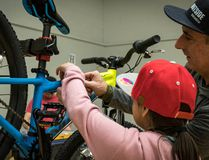 Supplied by Peter Dyck A student from Exshaw School helps one of the local volunteers, from Outside Bike and Ski, assemble one of the 25 bikes donated to the school last week.