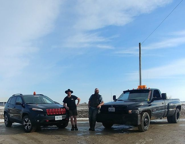 Jesse (right) and Josh, of Blyth, with their trusty roadside rescue vehicles. The men have used their SUV and truck, both equipped with caution lights and towing apparatus, to assist several drivers in need this winter. They hope to continue to serve the community in their own unique way. (PHOTO COURTESY OF JESSE BAARDA)