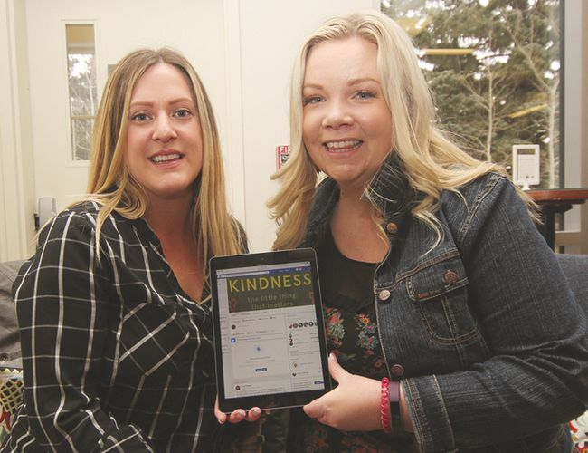 KASSIDY CHRISTENSEN HIGH RIVER TIMES/POSTMEDIA NETWORK. Rebecca Kyllo, left, and Jody Seeley, right, hold a tablet that shows the 52 Weeks of Kindness – High River Facebook page.
